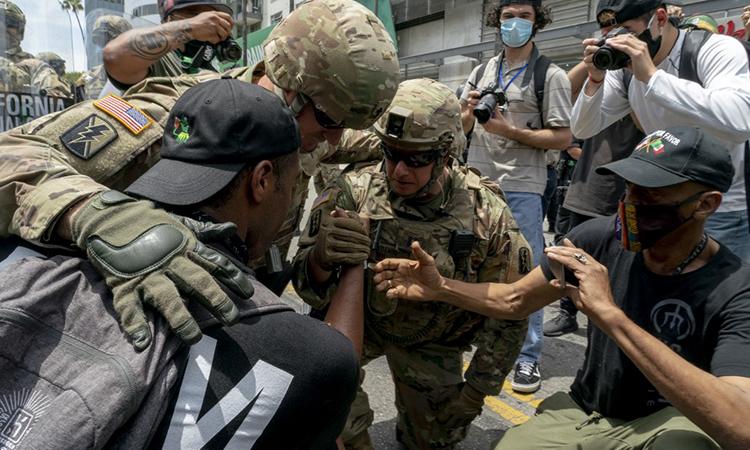 Vệ binh Quốc gia và người biểu tình quỳ gối trên đường phố Los Angeles, bang California, ngày 6/2. Ảnh: AFP.