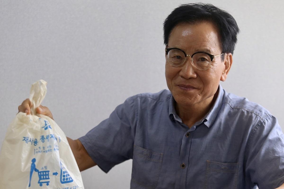 Ông Kim In Wan cầm trên tay túi đựng rác của Hàn Quốc. Ảnh: Gia Chính