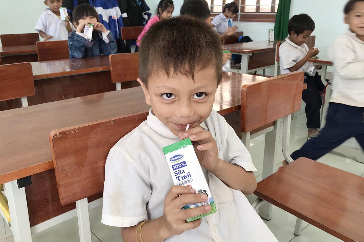 Em Nguyễn Hồ Khoa Viện, lớp 1trường Phổ thông Dân tộc bán trú tiểu học Trà Tập, huyện Nam Trà My vui mừng được uống sữa. Ảnh: Đắc Thành.