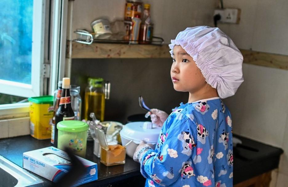 May Thu, 8 tuổi, nổi tiếng trên mạng xã hội vì nấu thành thạo nhiều món ăn như cà ri cá, ếch xào cay. Ảnh: AFP.