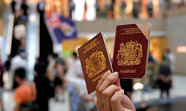 Một người cầm hai hộ chiếu BNO trong cuộc biểu tình phản đối luật an ninh ở Hong Kong tháng trước. Ảnh: Reuters.