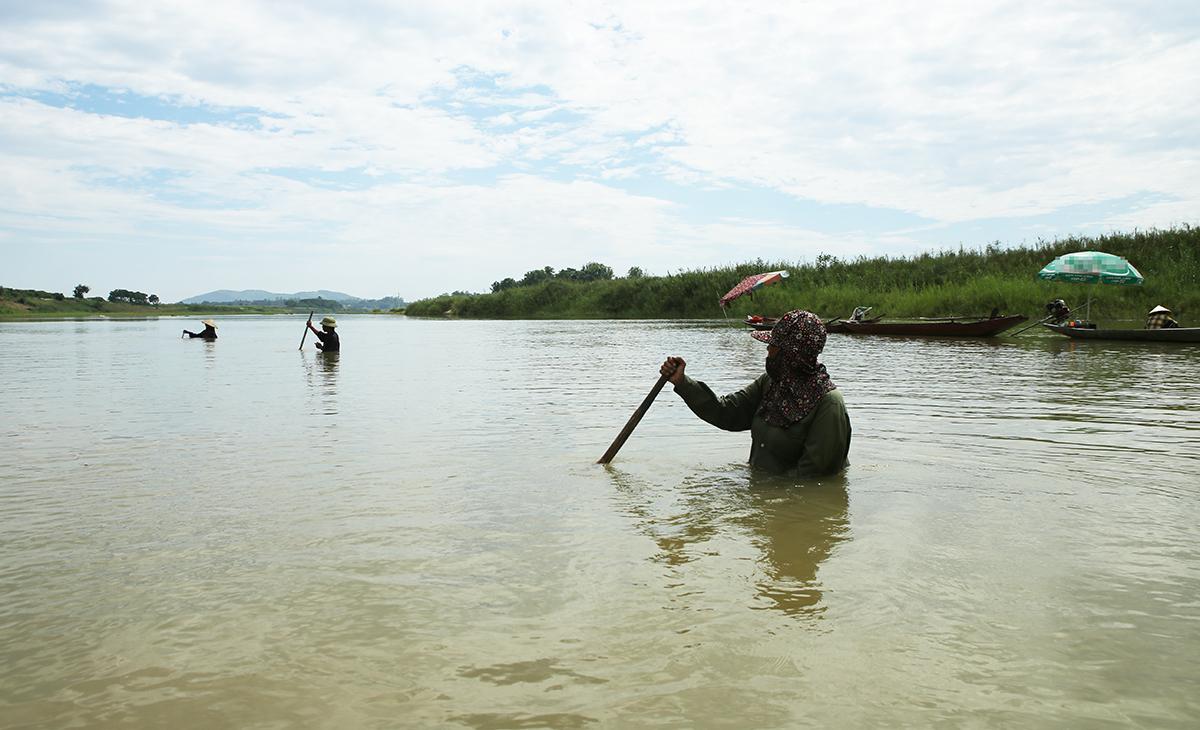 Nhiều người ngâm mình dưới sông sâu hơn một mét trong nhiều giờ để cào hến. Ảnh: Nguyễn Hải.