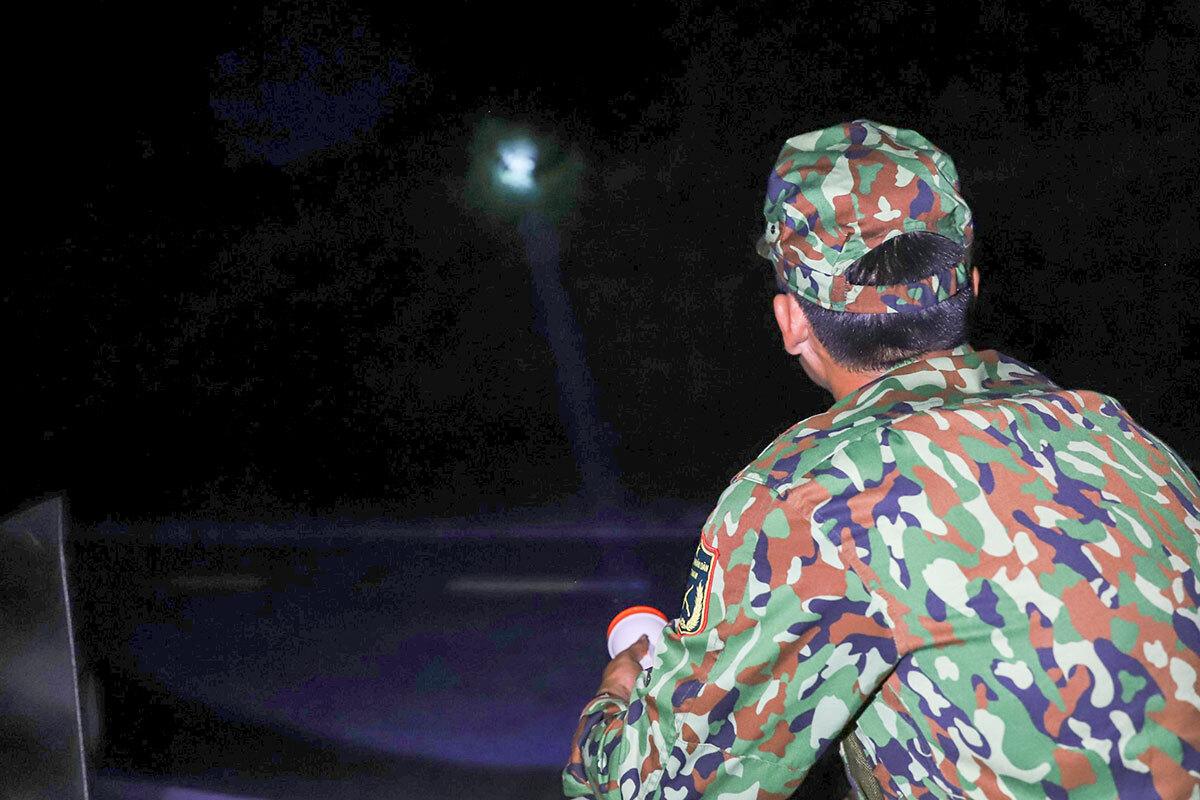 1h sáng 5/6, các chiến sĩ quân đội ngồi canh gác bên bìa rừng thường xuyên dọi đèn pin để kiểm soát. Ảnh: Nguyễn Đông.