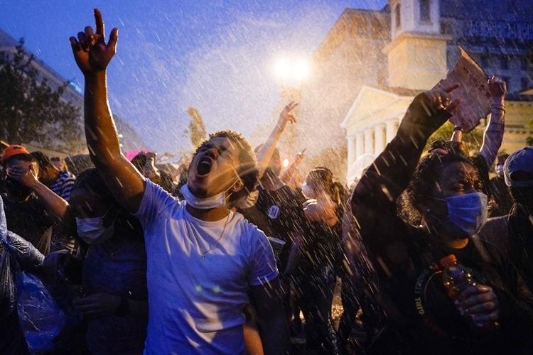 Người dân biểu tình trong mưa lớn ở thủ đô Washington tối 4/6. Ảnh: AP.