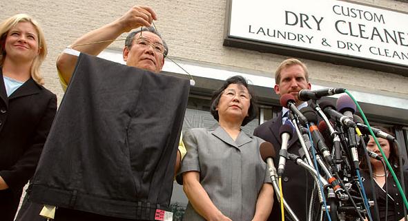 Jim Chung, chủ tiệm giặt là bị kiện, giơ cao chiếc quần gây ra tranh chấp. Ảnh:The New York Times.