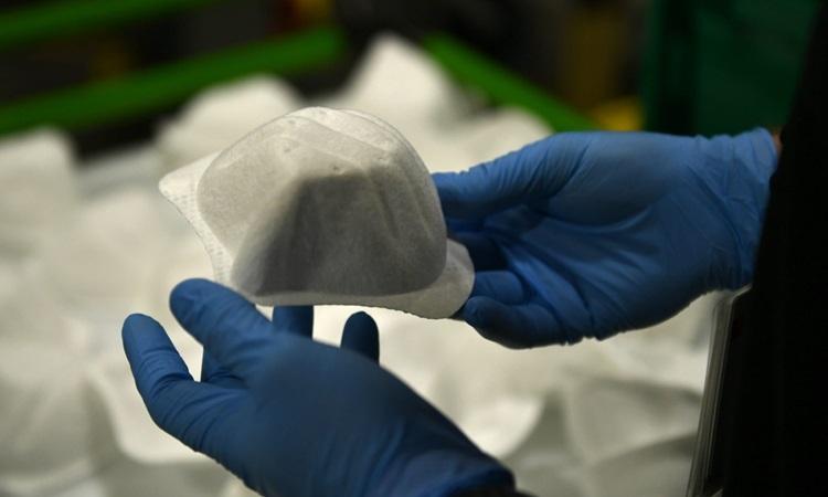 Nhân viên cầm một khẩu trang N95 tại nhà máy sản xuất thiết bị bảo hộ cá nhân ở bang Arizona, Mỹ hôm 5/5. Ảnh: AFP.