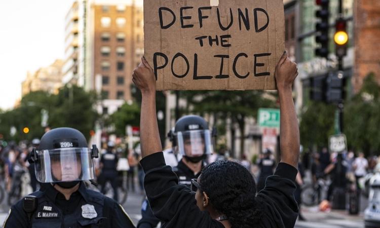 Người biểu tình giơ biểu ngữ cắt giảm ngân sách cho cảnh sát tại thủ đô Washington ngày 1/6. Ảnh: Reuters.