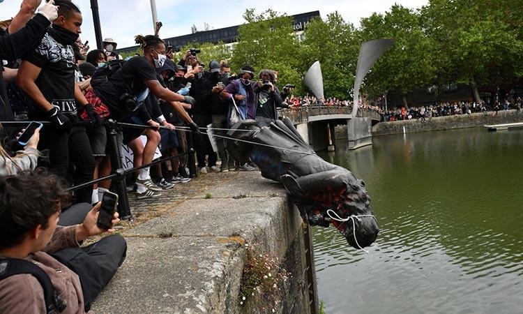 Người biểu tình đẩy tượng nhà buôn nô lệEdward Colston xuống sông hôm 7/6. Ảnh: PA.
