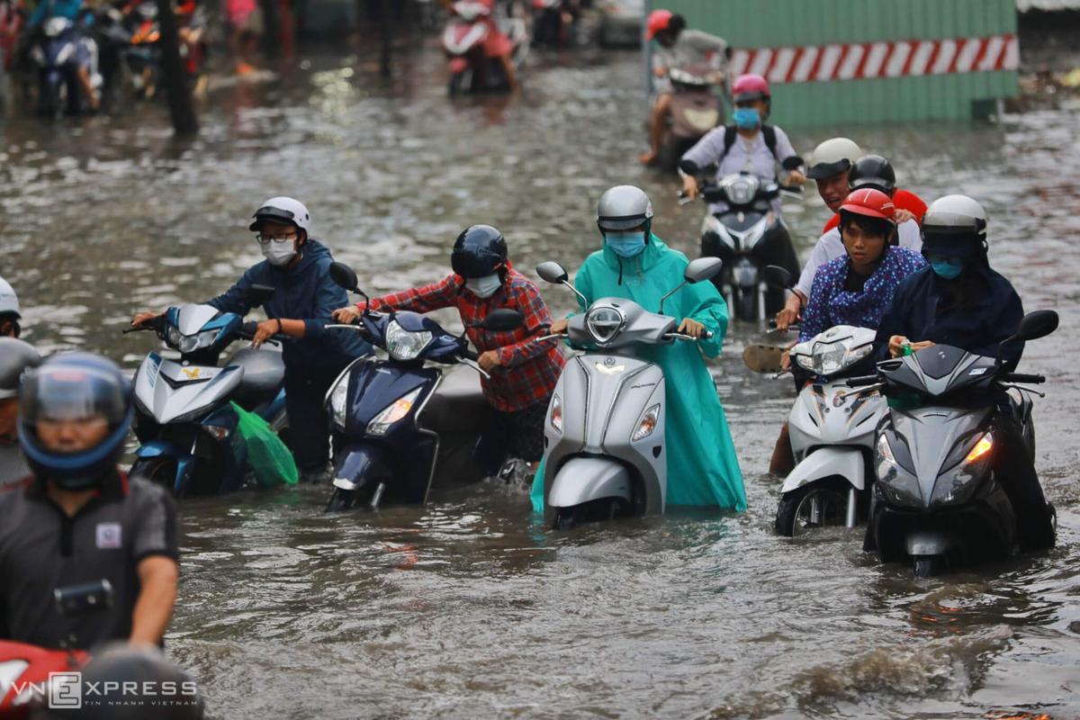 Đường Nguyễn Hữu Cảnh bị ngập sâu sau cơn mưa lớn chiều 3/6 khiến nhiều xe chết máy, người dân phải dắt bộ. Ảnh: Hữu Khoa.