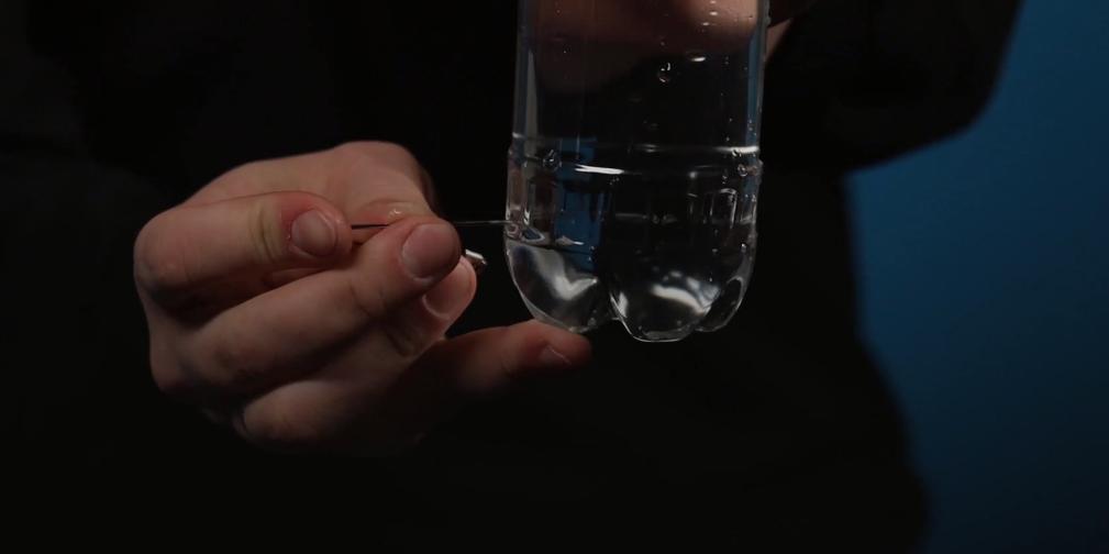 Dùngkim chọc lỗ nhỏ ở phần thân dưới của chai.