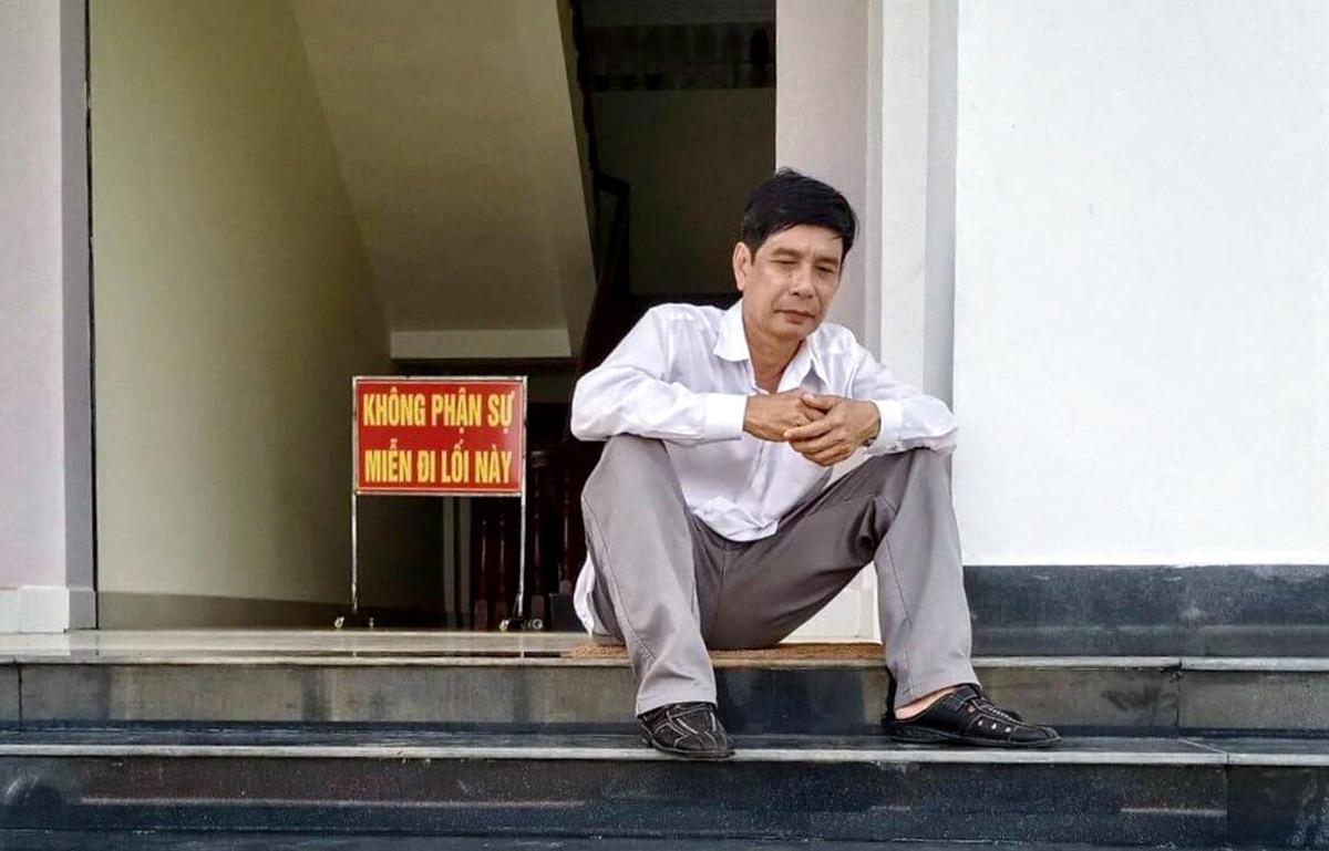 Ông Phước ngồi tại sân tòa trước lúc tuyên án sáng 29/5. Ảnh:Luật sư cung cấp.