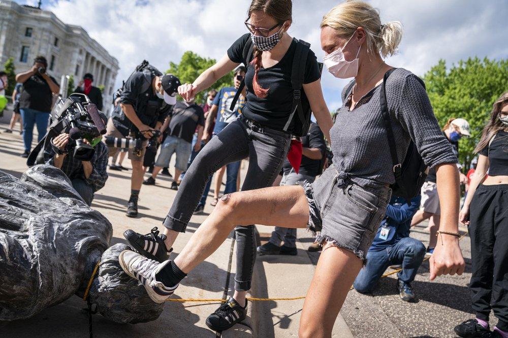 Người biểu tình dẫm lên tượng Christopher Columbus sau khi kéo đổ nó trước tòa quốc hội Minnesota ở St.Paul, bang Minnesota, hôm 10/6. Ảnh: AP.