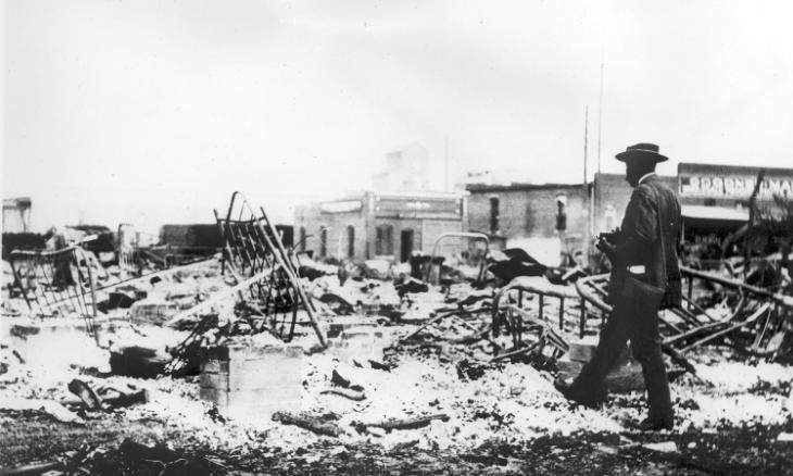 Một người Mỹ gốc Phi giữa đống tro tàn sau vụ bạo loạn năm 1921. Ảnh: Oklahoma Historical Society.