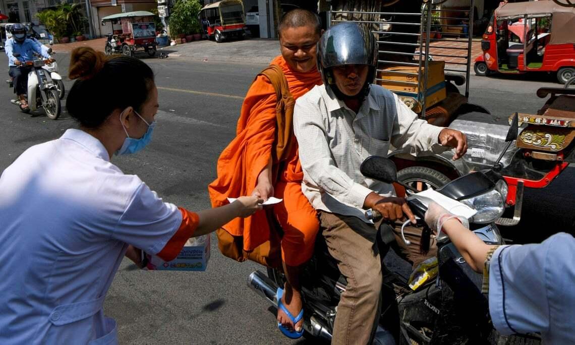 Tình nguyện viên phát khẩu trang miễn phí cho người dân trên một con đường ở Phnom Penh, Campuchia, hồi tháng 1. Ảnh: AFP.