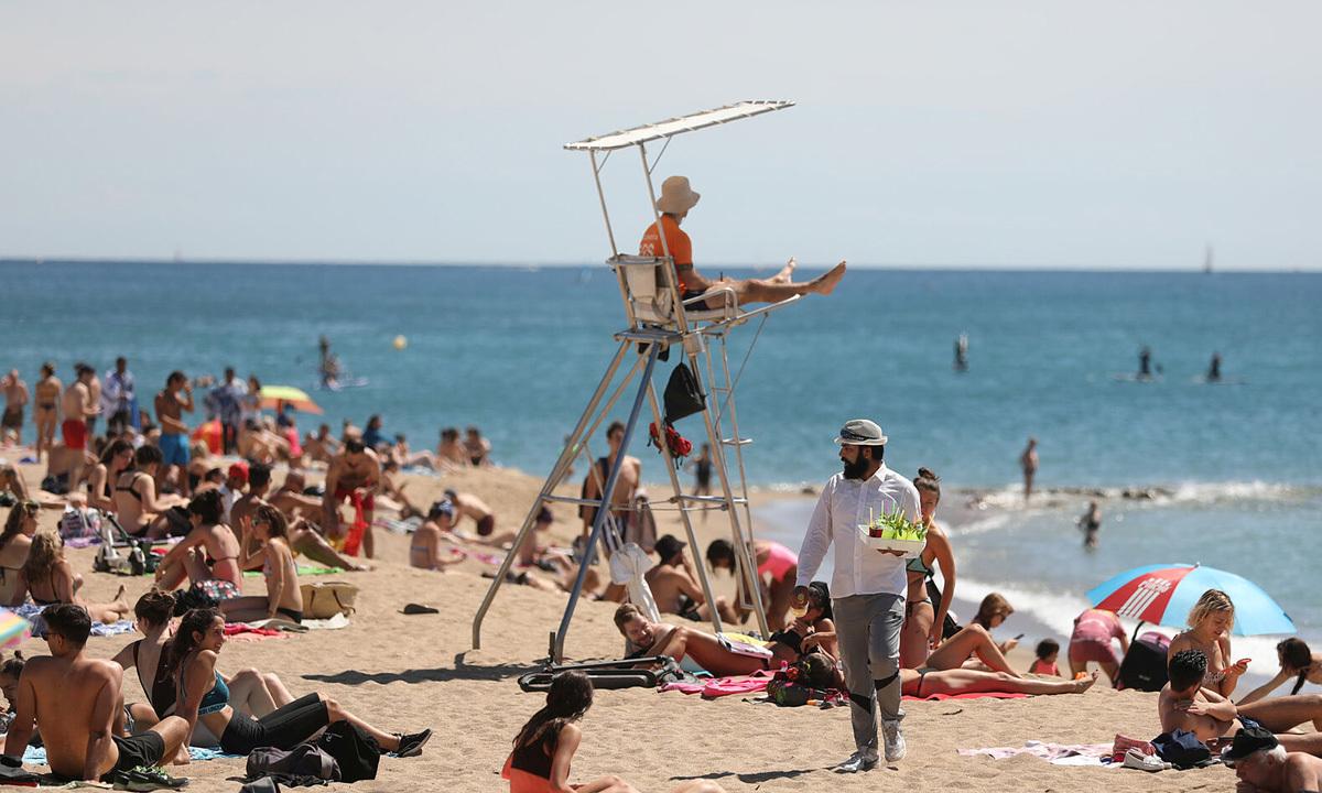 Người dân tận hưởng ánh nắng tại bãi biểnBarceloneta, thành phố Barcelona, Tây Ban Nha, hôm 13/6. Ảnh: Reuters.