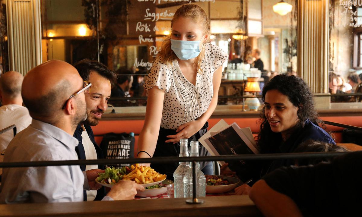 Thực khách dùng bữa trưa trong một nhà hàng tại Paris, Pháp, hôm 15/6. Ảnh: Reuters.