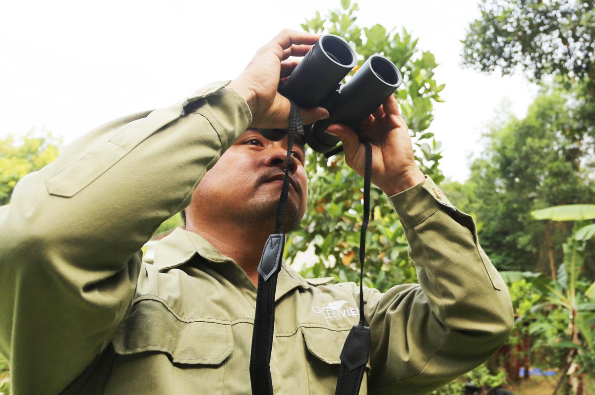 Ông Nguyễn Dư dùng ốm nhòm quan sát đàn voọc ở núi Hòn Dồ. Ảnh: Đắc Thành.
