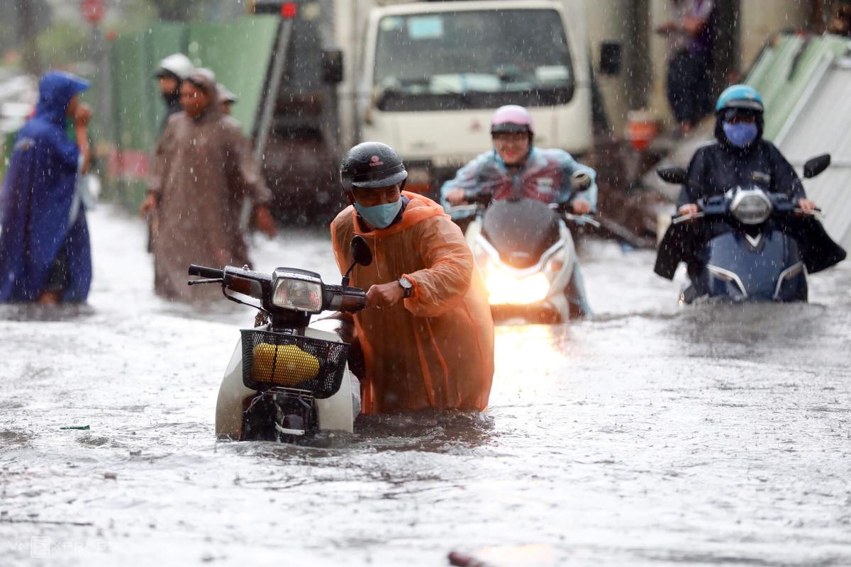 Người dân dắt xe chết máy trong cơn mưa lớn chiều 16/6 trên đường Nguyễn Hữu Cảnh (quận Bình Thạnh). Ảnh: Hữu Khoa.