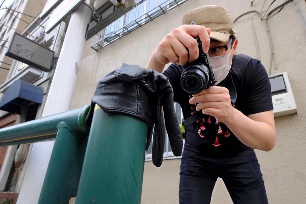 Ishii chụp ảnh một chiếc găng tay thất lạc vắt trên hàng rào vệ đường ở Tokyo hôm 25/5. Ảnh: AFP.