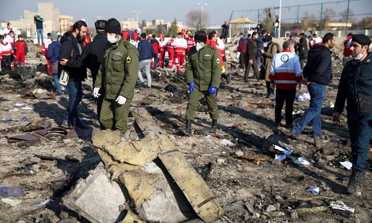 Nhân viên an ninh và thành viên của hội trăng lưỡi liềm đỏ tại hiện trường vụ máy bay rơi ở Iran hôm 8/1. Ảnh: Reuters.