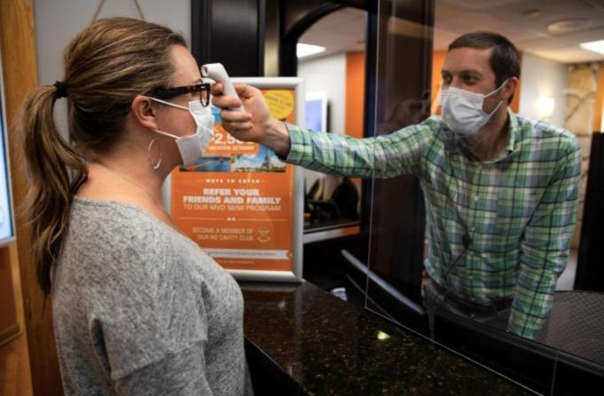 Nửa nước Mỹ nới lỏng lệnh phong tỏa vào ngày 1/5 vừa qua. Một nhân viên cơ sở nha khoa ở thành phố Columbus, bang Ohio, kiểm tra thân nhiệt của khách hàng khi tái mở cửa. Ảnh: Reuters.