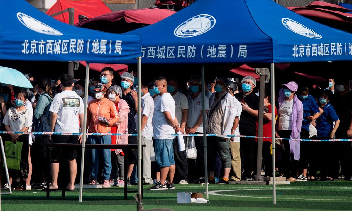 Người dân sống gần hoặc từng đến chợ đầu mối nông sản Tân Phát Địa xếp hàng chờ xét nghiệm tại sân vận động hôm 16/6. Ảnh: AFP.