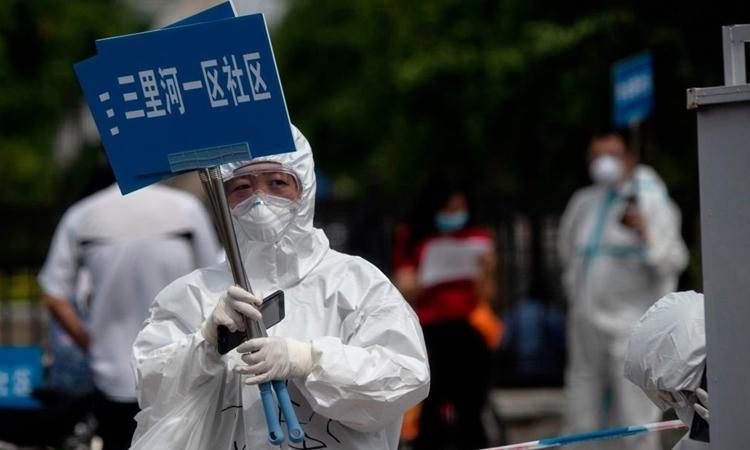 Nhân viên y tế giơ biển để hỗ trợ người sống gần hoặc từng đến chợ Tân Phát Điạ ở Bắc Kinh ngày 17/6. Ảnh: AFP.