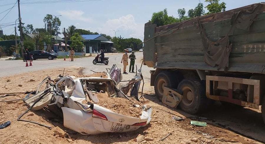 ChiếcToyota Vios bẹp nát sau khi bị xe tải chở đất tông trúng, đè lên. Ảnh: Lam Sơn.