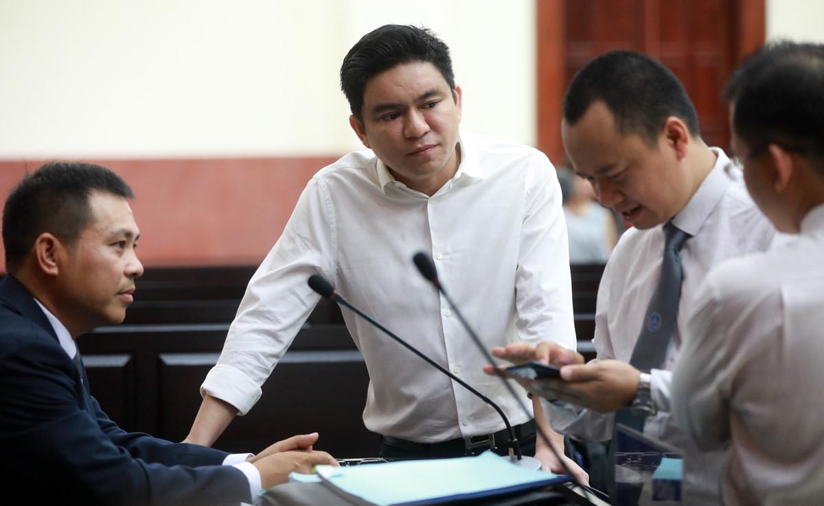 Bác sĩ Chiêm Quốc Thái (giữa) trao đổi với các luật sư trước phiên xử sáng 19/6. Ảnh: Hữu Khoa.