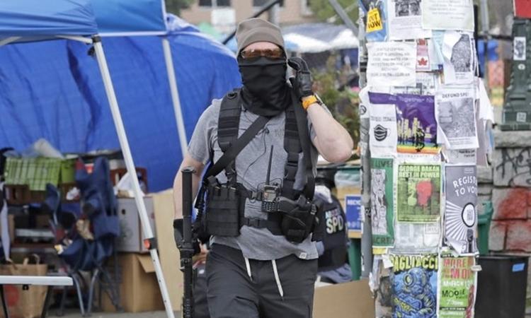M?t tình nguy?n viên c?m súng t?i CHOP ? Seattle ngày 20/6. ?nh: AP.