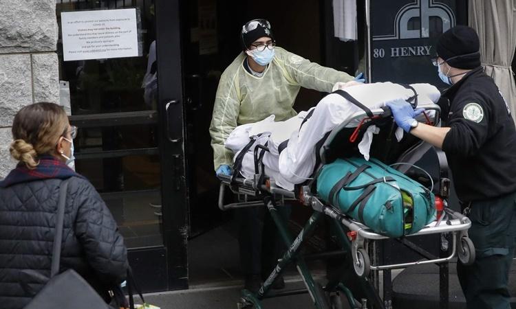 Nhân viên y tế di chuyển một bệnh nhân nghi nhiễm nCoV ở Brooklyn, New York, ngày 17/4. Ảnh: AP.