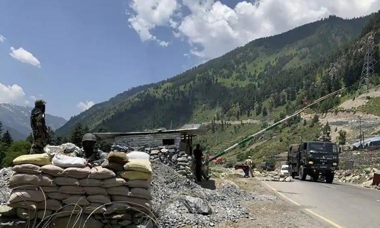Lực lượng bán quân sự Ấn Độ đứng gác khi đoàn xe quân đội Ấn Độ di chuyển trên đường cao tốc Srinagar-Ladakh ngày 18/6. Ảnh: AP.