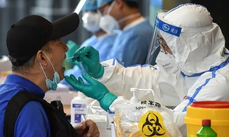 Nhân viên y tế lấy mẫu xét nghiệm nCoV cho một người dân ở thành phố Nam Kinh, tỉnh Giang Tô, Trung Quốc, ngày 15/6. Ảnh: AFP.