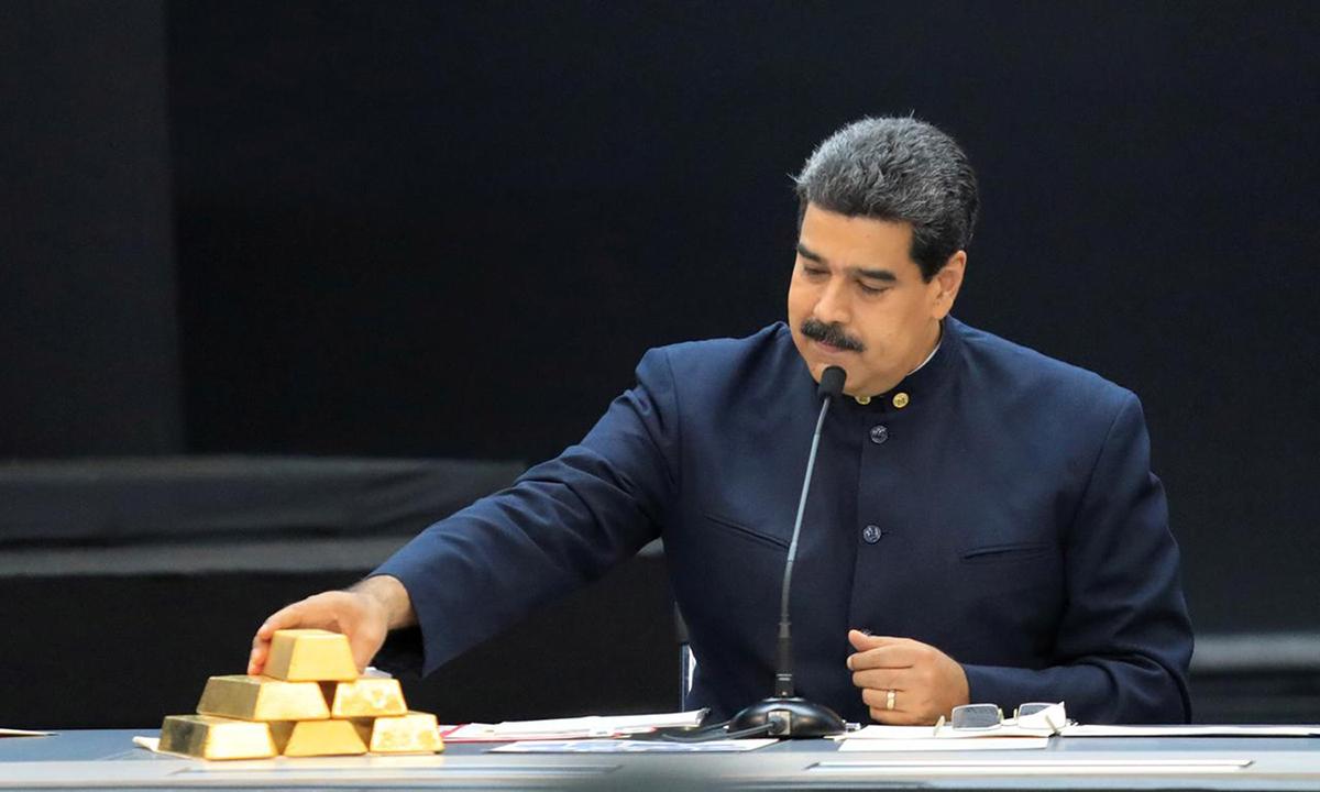 Tổng thống Nicolas Maduro chạm tay vào thỏi vàng khi họp với các bộ trưởng ở Caracas, tháng 3/2018. Ảnh: Reuters.