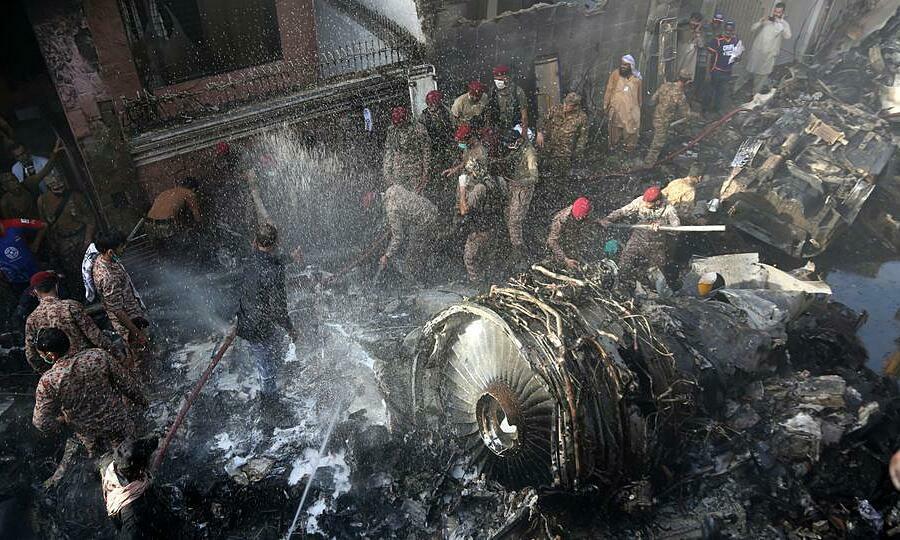 Binh sĩ và nhân viên cứu hộ Pakistan tìm kiếm nạn nhân gần động cơ của chiếc Airbus A320 gặp nạn ở Karachi, ngày 22/5. Ảnh:AFP.