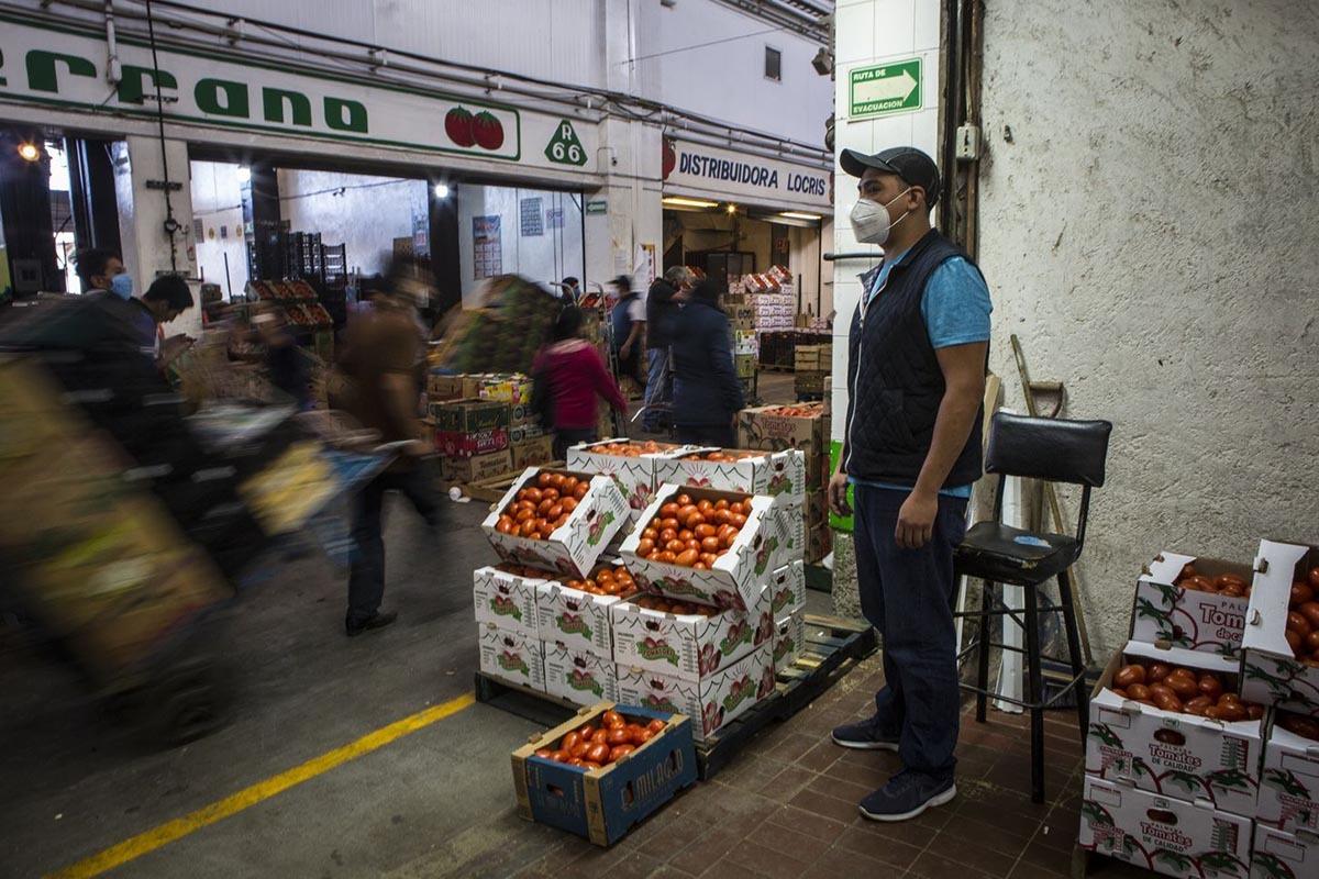 Carlos Mateo, con trai Martin Mateo, đứng tại lối vào gian bán cà chua của gia đình tại chợ Central deAbasto. Ảnh: Washington Post.