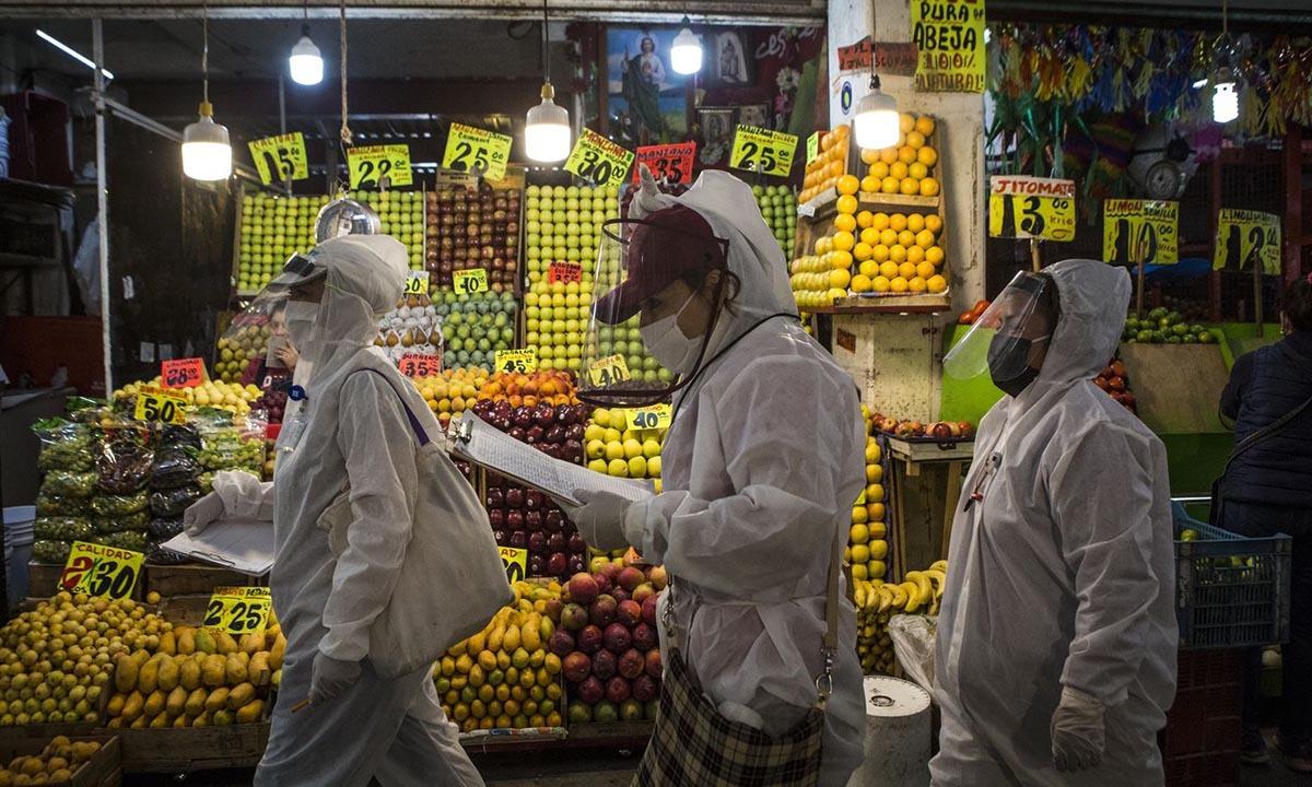 Các nhân viên y tế đi quanh chợCentral de Abasto tại Mexico City, Mexico, để đo thân nhiệt mọi người. Ảnh: Washington Post.