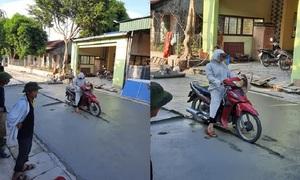 Cô gái cười gượng khi đi vào đường vừa đổ bê tông