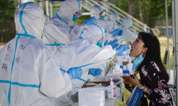 Nhân viên y tế lấy mẫu xét nghiệm nCoV cho một người dân ở thủ đô Bắc Kinh, Trung Quốc, ngày 20/6. Ảnh: Reuters.