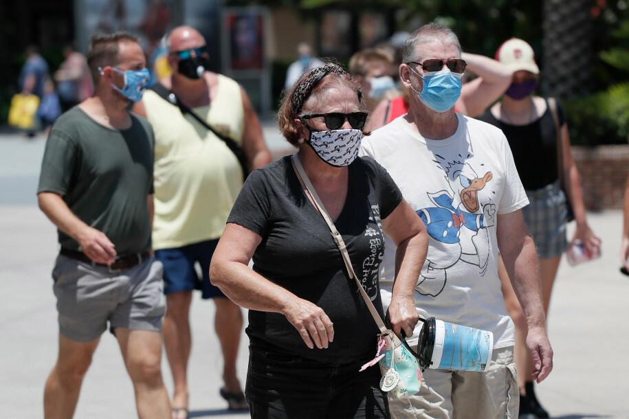 Người dân đeo khẩu trang trên đường phố ở Lake Buena Vista, Florida, Mỹ. Ảnh: AP