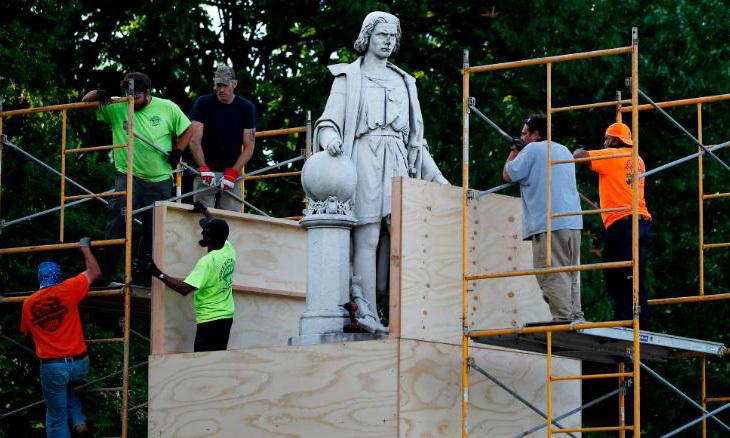 Các công nhân đóng thùng gỗ quanh tượng Christopher Columbus ở Philadelphia, Mỹ, hôm 16/6 để bảo vệ nó. Ảnh: AP.