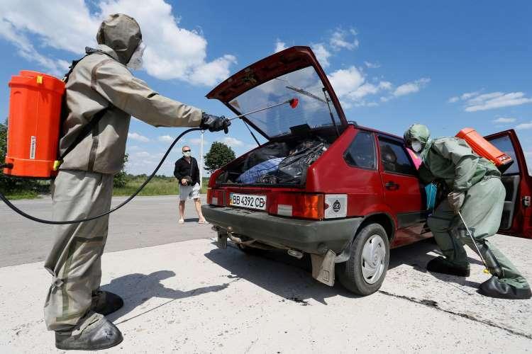Chuyên gia mặc đồ bảo hộ khử trùng một chiếc xe hơi ở tỉnhDonetsk, Ukraine, hôm 25/6. Ảnh: Reuters.
