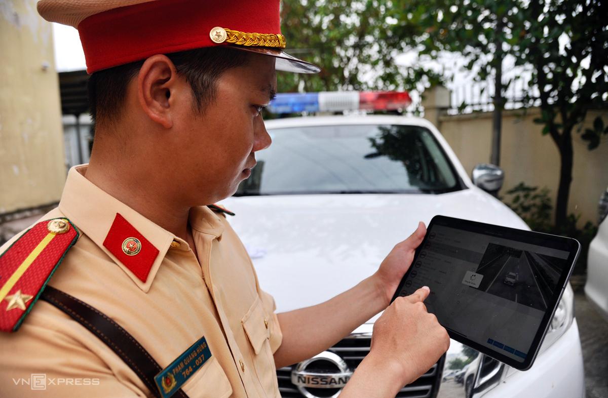 Cán bộ thuộc Cục CSGT kiểm tra lỗi vi phạm của tài xế ôtô trên máy tính bảng. Ảnh: Sơn Hải