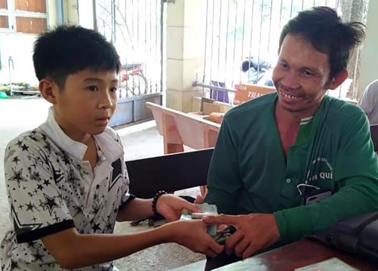 Em Hồ Thiế Thuận trao lại số tiền nhặt được cho ông Phan Thanh Nhàn. Ảnh: An Phú