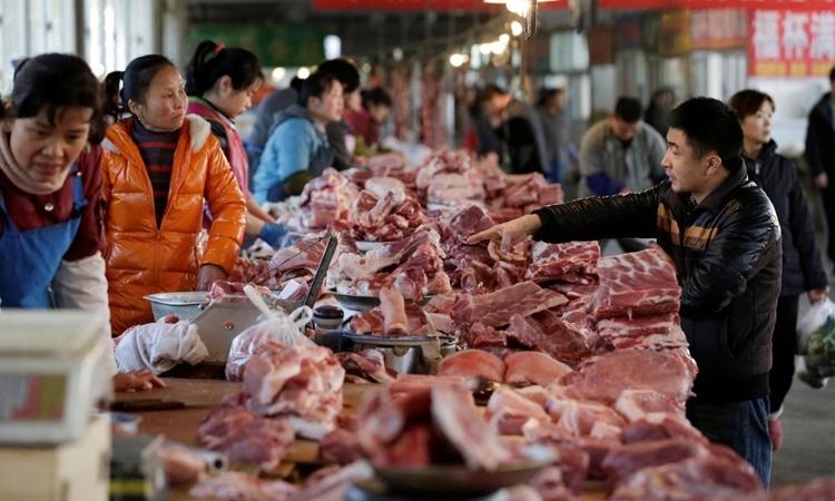 Các sạp bán thịt lợn tại một khu chợ ở Bắc Kinh, Trung Quốc. Ảnh: Reuters.