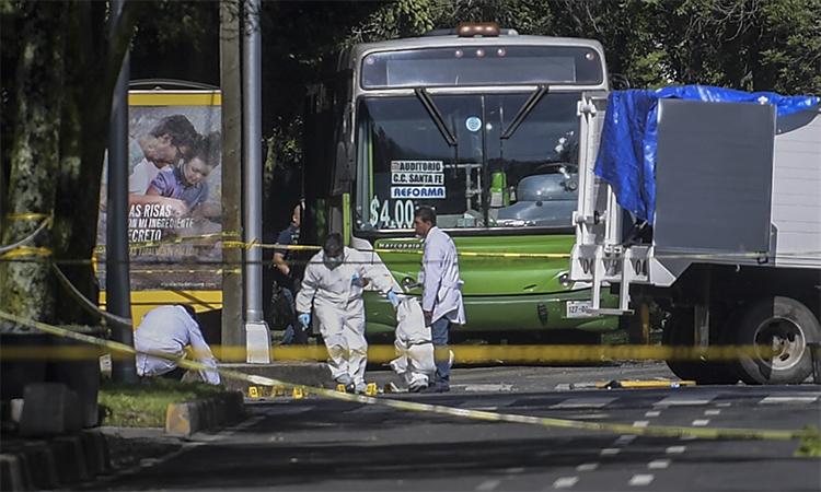 Nhân viên khám nghiệm hiện trường tại nơi xảy ra vụ tấn công nhằm vào xe chở cảnh sát trưởng Mexico City, ngày 26/6. Ảnh: AFP.