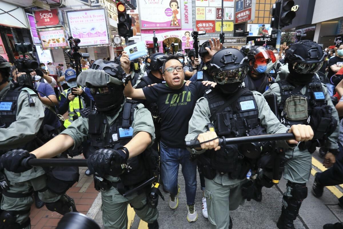 Một người biểu tình Hong Kong (áo phông đen) bị cảnh sát bắt hồi tháng 5. Ảnh: SCMP.