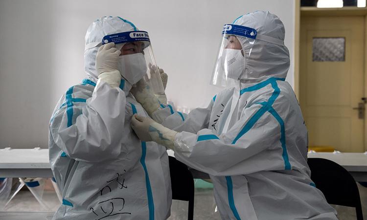 Nhân viên y tế mặc trang phục bảo hộ trước khi đi lấy mẫu xét nghiệm nCoV tại khu tài chính phố Kim Dung, Bắc Kinh, Trung Quốc, ngày 24/6. Ảnh: AFP.