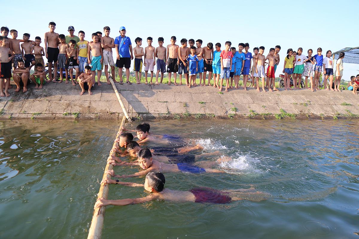 Đám học trò đứng xem một nhóm thực hành cách đập chân ở lớp dạy bơi của thầy Tước. Ảnh: Hoàng Táo