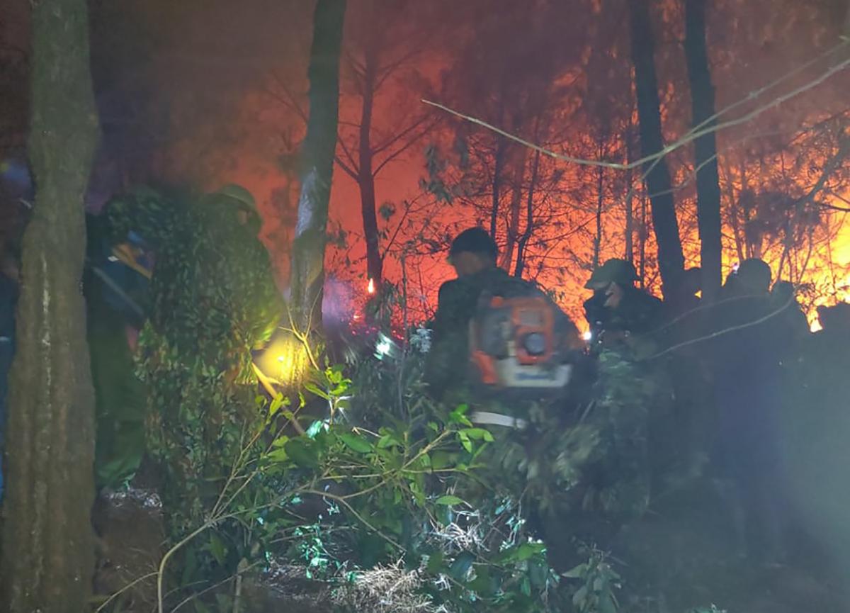 Tốp bộ đội biên phòng Nghệ An nỗ lực khống chế đám cháy tại xã Diễn An đêm 29/6. Ảnh: Hải Thượng.